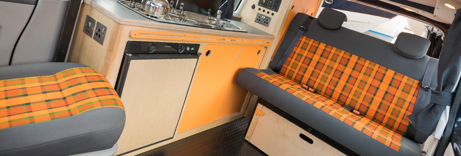 grey and orange tarten rock and roll bed in campervan with lots of storage space and built in fridge and kitchen units