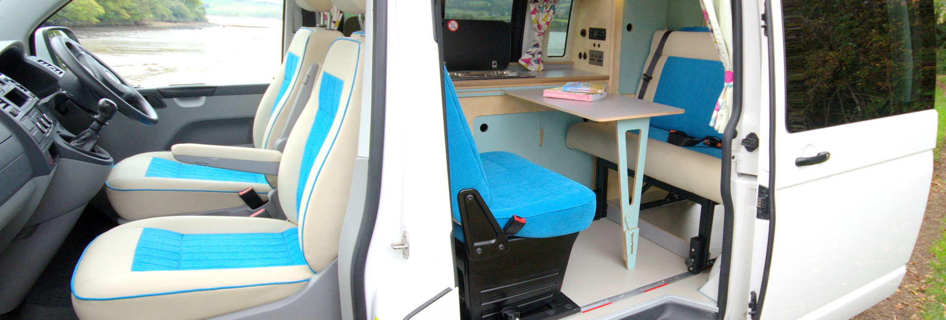 cool campervan conversion with white and blue seats, eco plywood units in light blue and clever fold away table