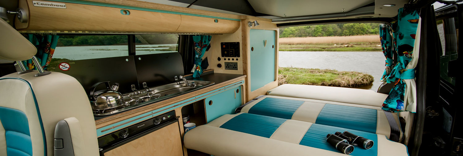 rock and roll blue and white flat down bespoke bed in campervan eco bespoke conversion looking out to beautiful view