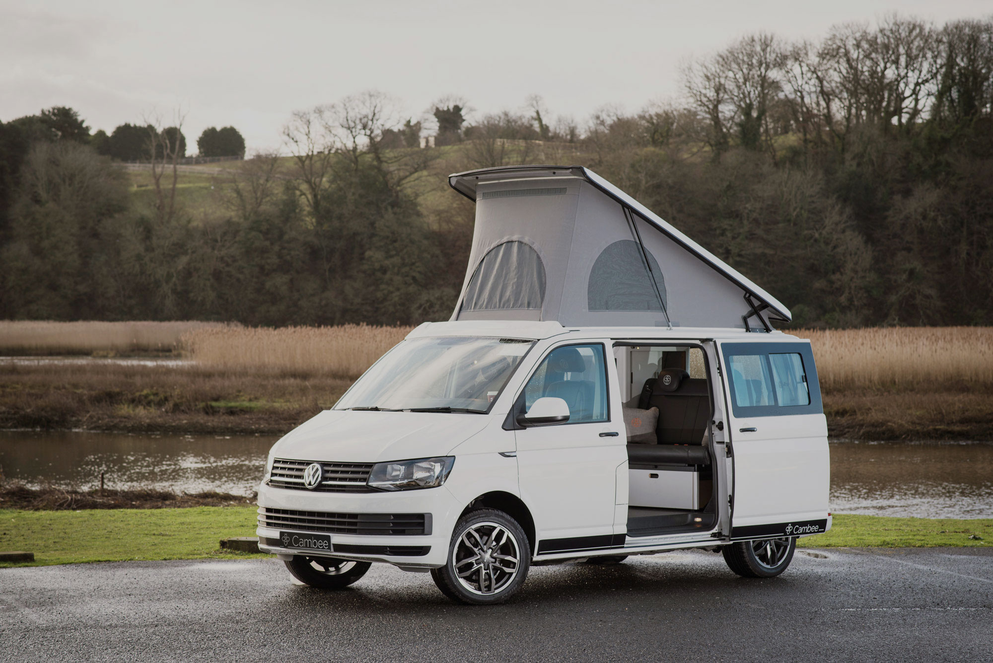 T6 VW white slick campervan with alloy wheels parked in nature with elevated roof and side door open