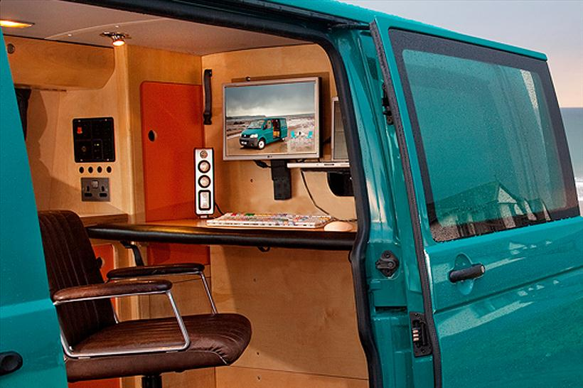 VW campervan parked at the beach with portable office editing suite plywood eco conversion, swivel chair with side door open