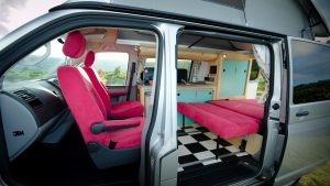Cool blush pink campervan conversion interior with eco birch plywood blue cupboards and funky chequered floor from the side doors parked in nature