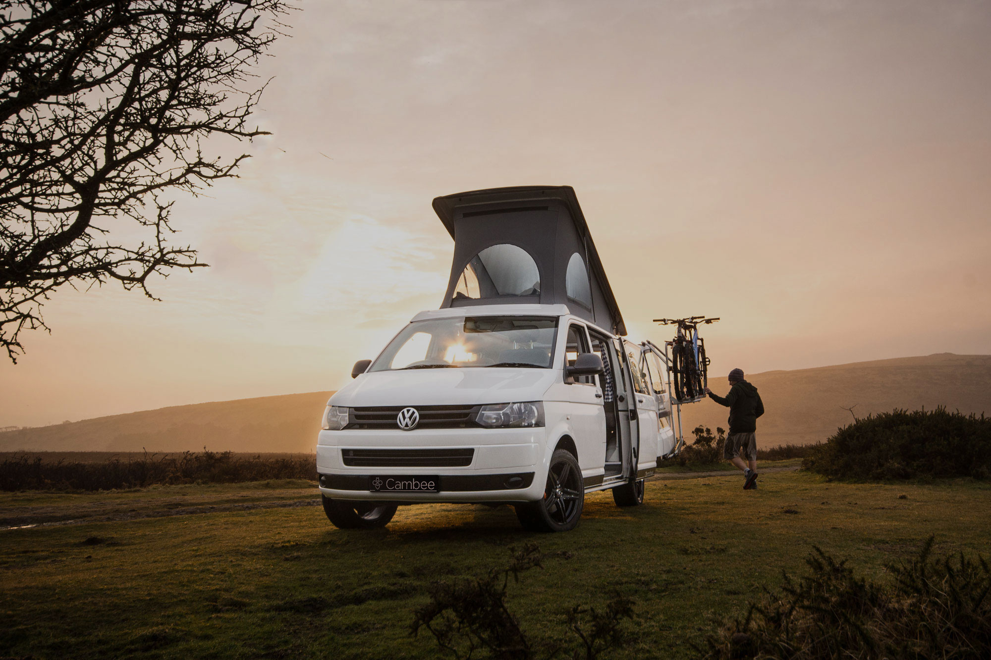 White T5 VW campervan parked by in nature, with bike rack with the roof elevated and side door open during beautiful sunset