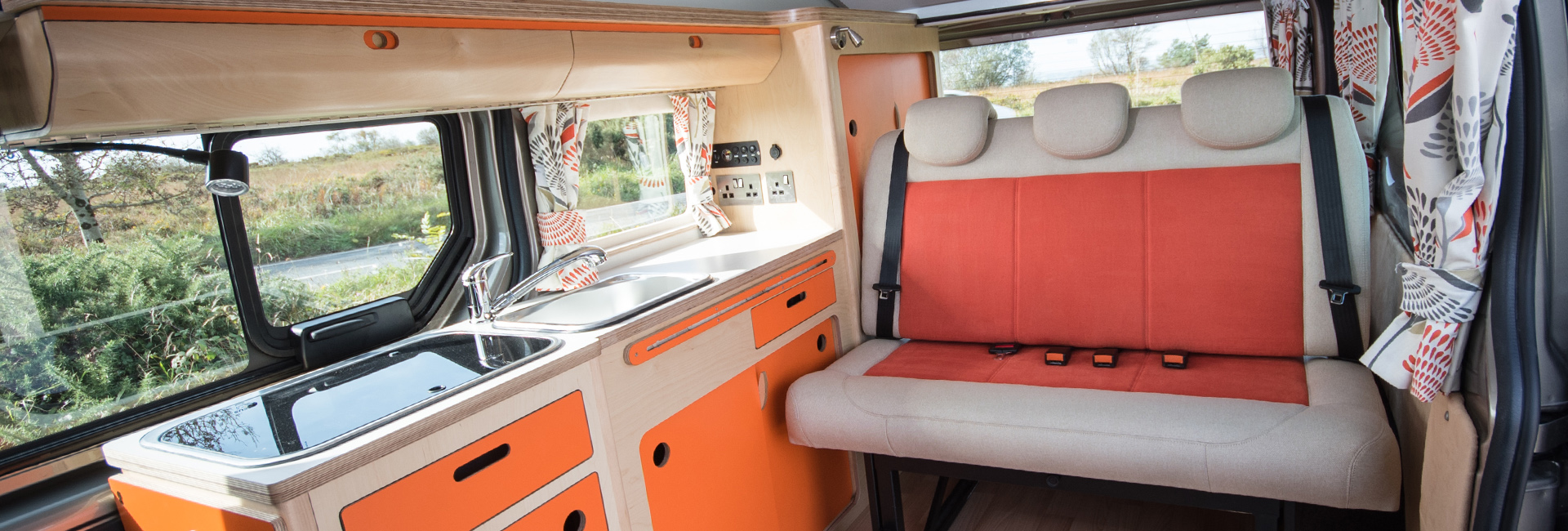 bright fresh campervan eco plywood conversion in orange and cream with rock and roll bed, built in fridge, sink, gas hob, clever storage parked in nature