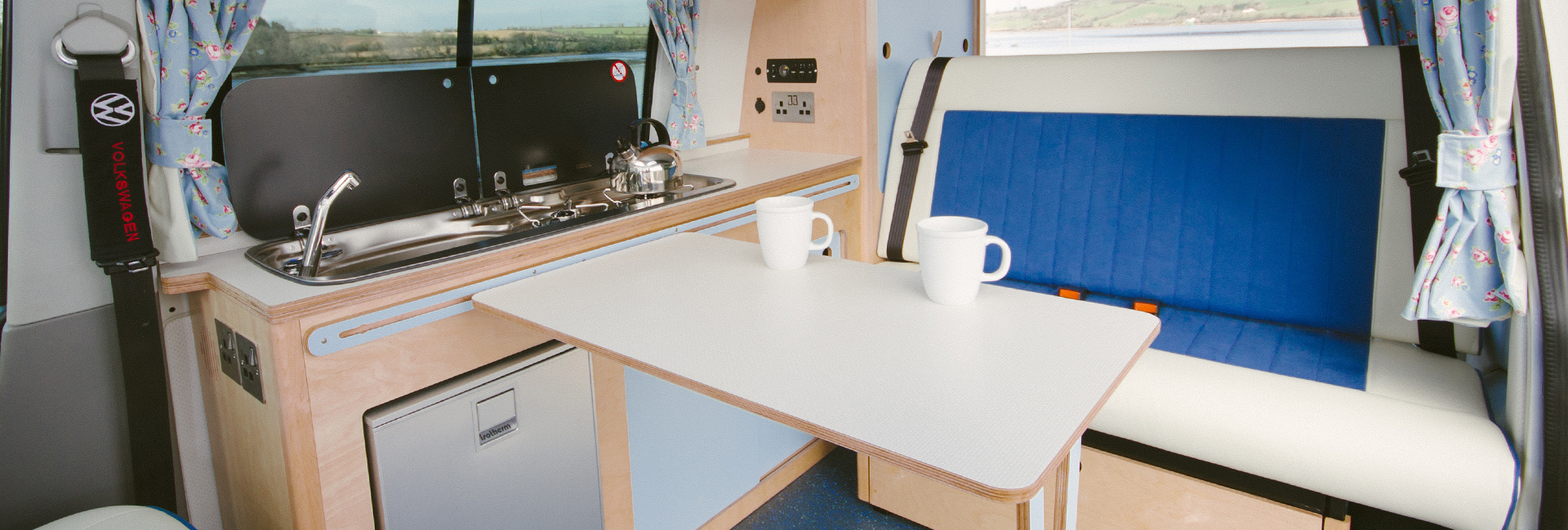 bright fresh campervan eco plywood conversion in white and blue with rock and roll bed, built in fridge, sink, gas hob, fold away table, clever storage parked in by beautiful sea