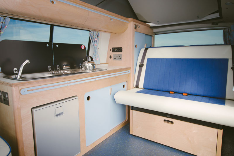bright fresh campervan eco plywood conversion in white and blue with rock and roll bed, built in fridge, sink, gas hob, elevated roof, clever storage