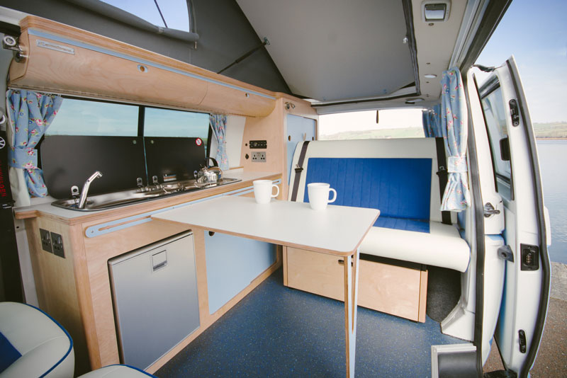 bright fresh campervan eco plywood conversion in white and blue with rock and roll bed, built in fridge, sink, gas hob, elevated roof, fold away table, clever storage parked in by beautiful sea