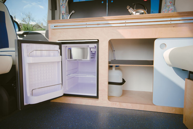 plywood kitchen units in light blue showing fridge and water storage space in campervan