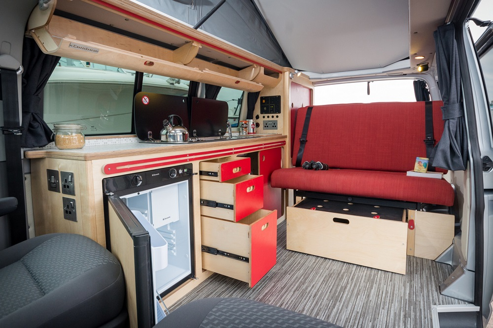 campervan eco plywood red conversion with rock and roll bed, built in fridge, overhead lockers, sink, gas hob, draws open showing clever storage, elevated roof with vinyl floor