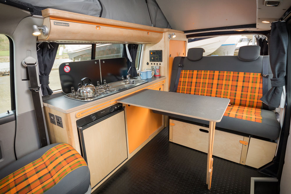rock and roll grey and orange tarten bespoke bed in campervan eco bespoke conversion with kitchen and wardrobes, clever adjustable fold away table, built in fridge, gas hob, sink and overhead lockers
