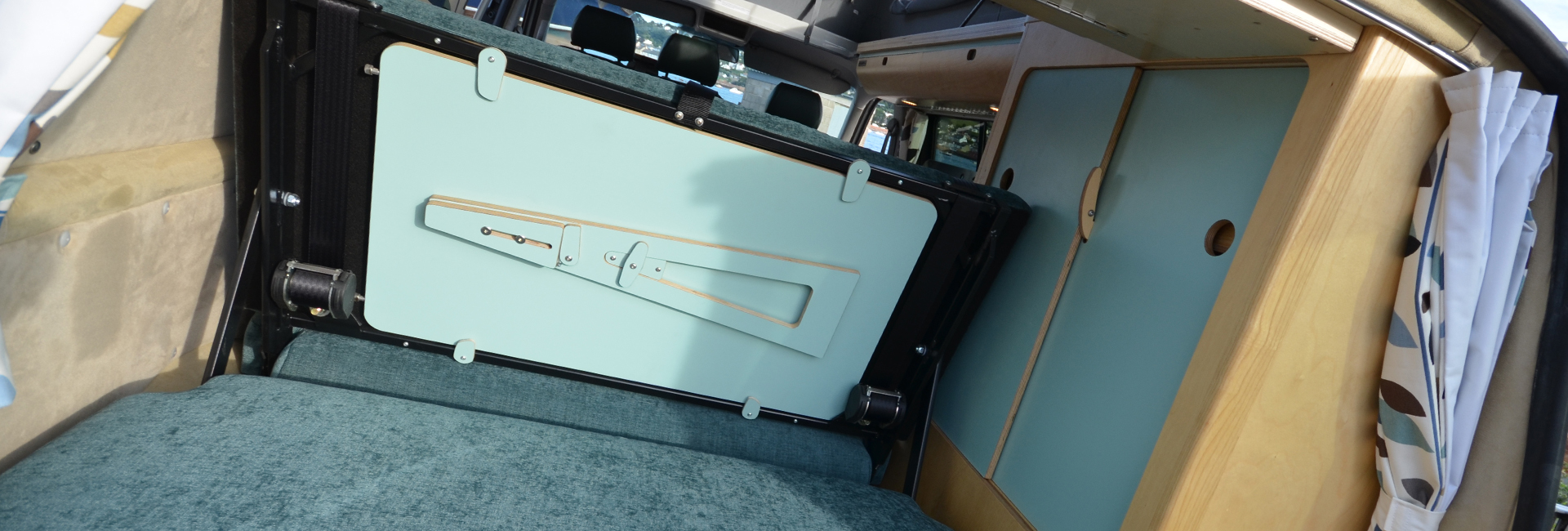 cool blue rear view of rock and roll bed and plywood wardrobes with clever fold away bespoke table stowed away in campervan