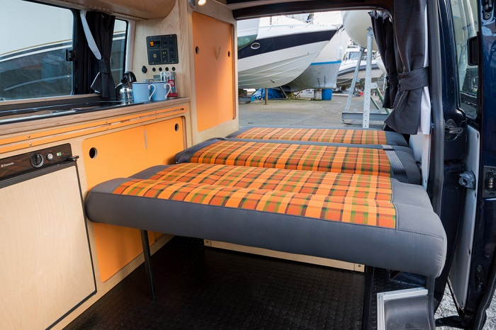rock and roll grey and orange tarten flat down bespoke bed in campervan eco bespoke conversion with kitchen and wardrobes