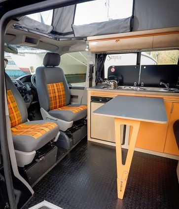 rock and roll grey and orange in campervan eco bespoke conversion with kitchen, clever adjustable fold away table, built in fridge, gas hob, sink and overhead lockers