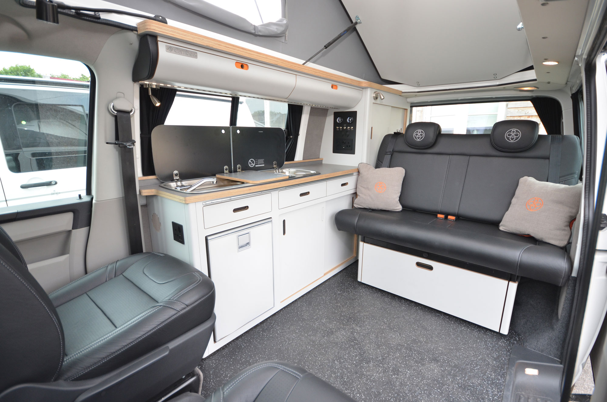 cool modern smart campervan eco plywood conversion in black leather and white units with rock and roll bed, built in fridge, overhead lockers, sink, gas hob, clever storage, embroidered cushions
