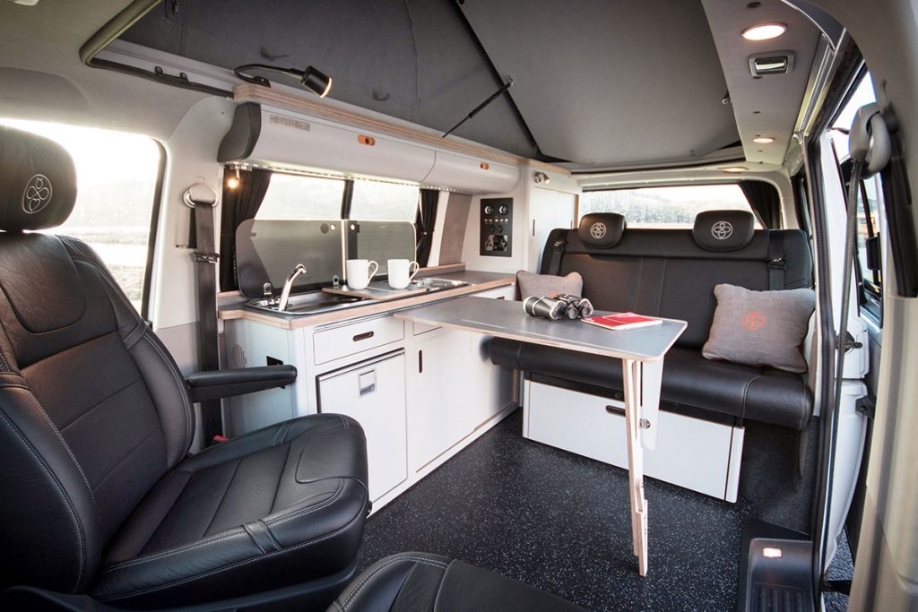 white eco birch plywood built in campervan cosy conversion with clever underseat storage solutions, overhead lockers, built in fridge, sink, clever fold away adjustable table, gas hob and cool leather seats