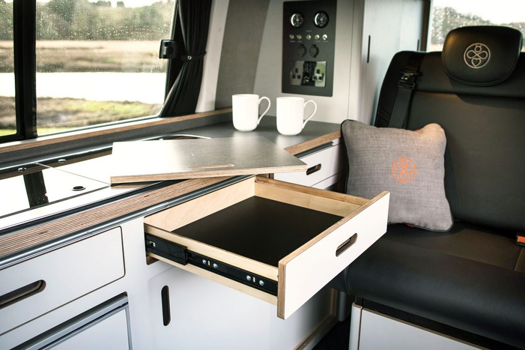 white eco birch plywood built in campervan cosy conversion with sink, gas hob, kitchen drawer open and cool leather seats