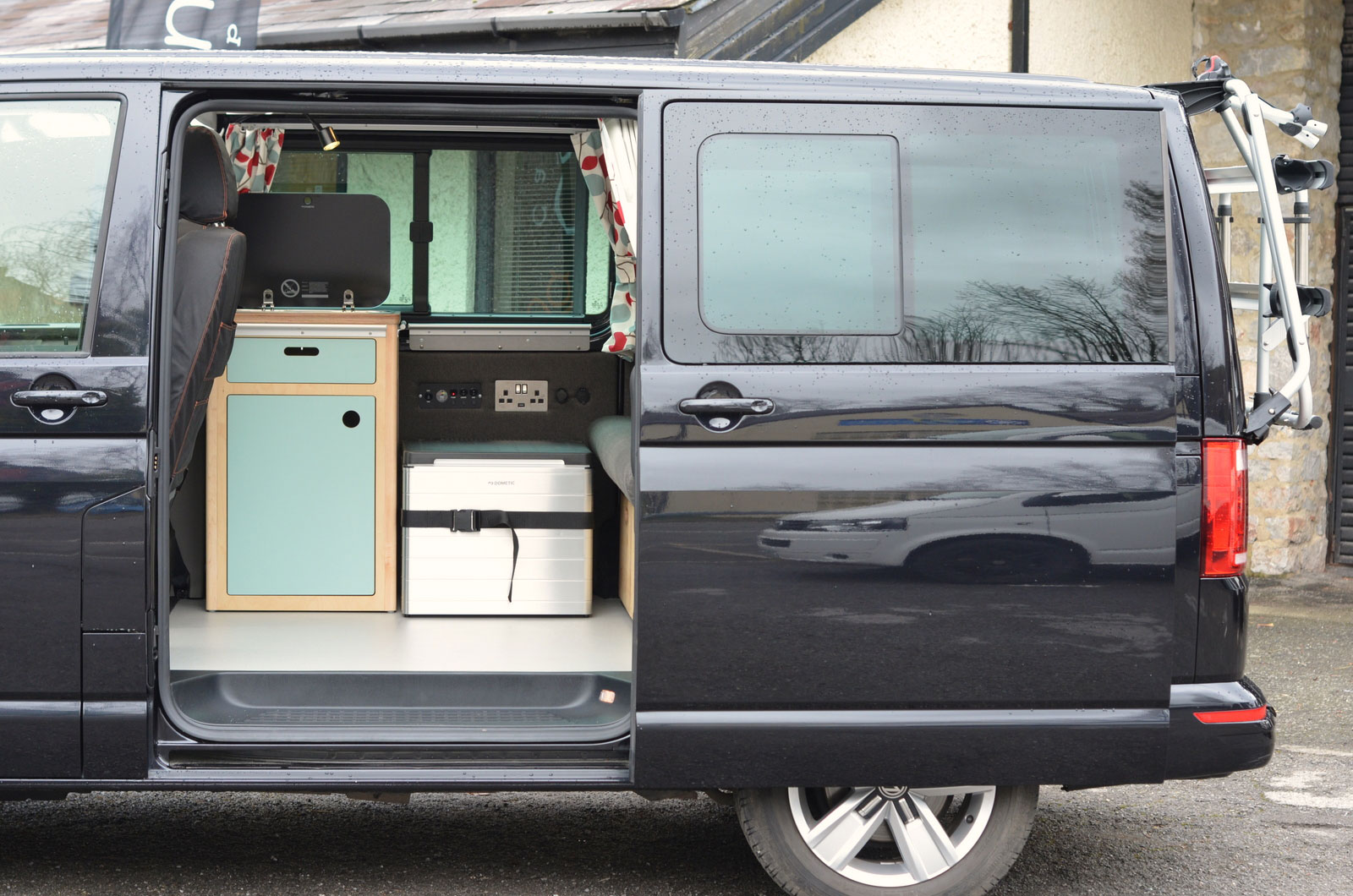Side view of free-standing bespoke plywood kitchen unit and cool box in campervan