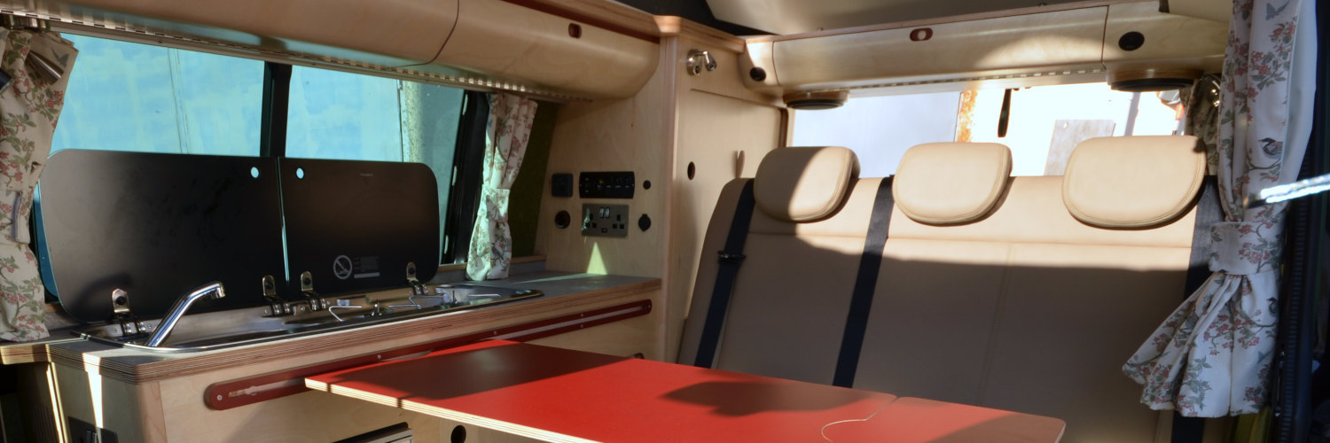 Interior of campervan with bespoke plywood kitchen, storage and fold-away table in the sunshine