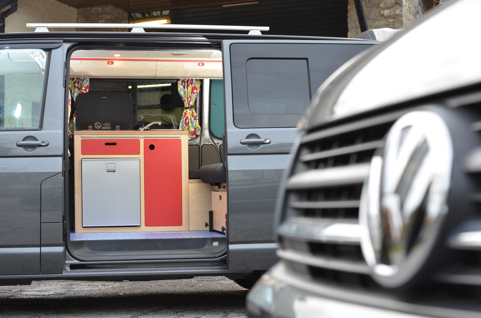 Side view of freestanding bespoke campervan red plywood kitchen unit with sink, built-in fridge freezer and gas hob and close up of VW logo