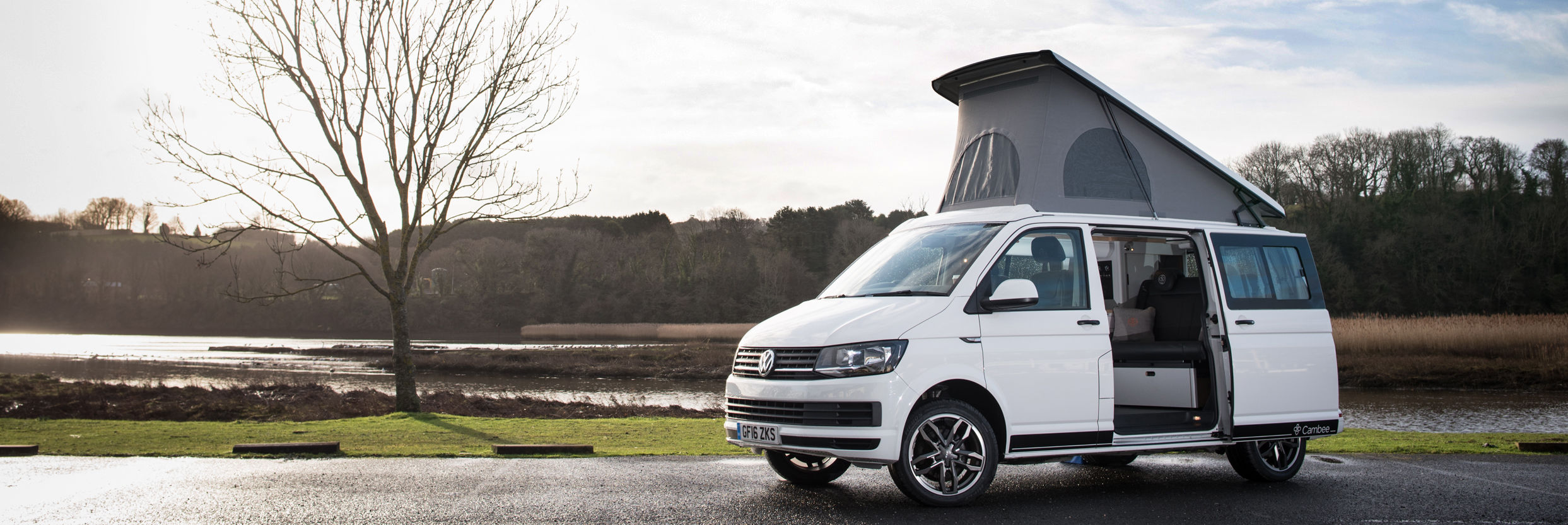 T6 VW white campervan conversion parked in nature beside lake with pop up roof and side door open