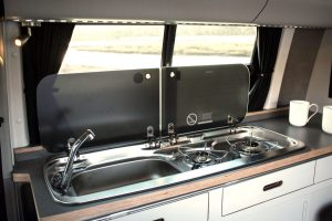 Stainless steel sink and gas hobs in bespoke campervan eco kitchen