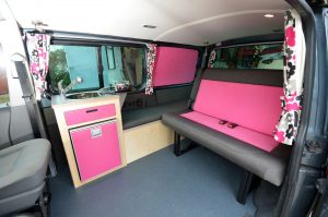 Campervan conversion showing bright pink and grey campervan interior and funky curtains