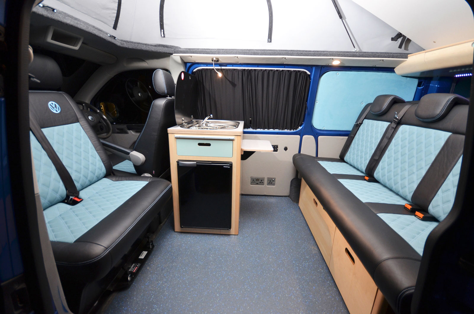 Inside campervan with sleek leather black and blue seating and kitchen cabinets and stand-alone kitchen unit