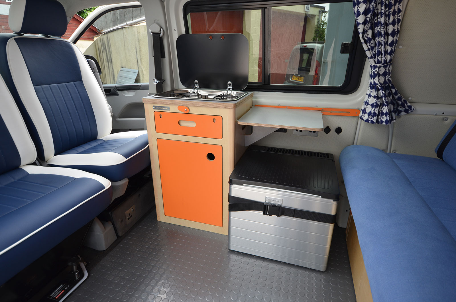 two tone leather seats in van conversion showing freestanding orange kitchen unit and mobile cool box