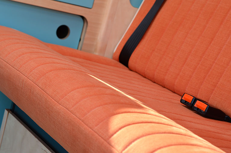 Bright orange seats in campervan with white piping against bespoke light blue plywood cupboards