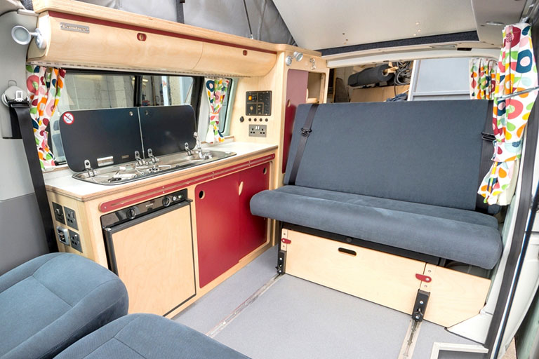 bespoke campervan conversation with red kitchen bespoke plywood units and rock and roll grey bed with funky bright curtains