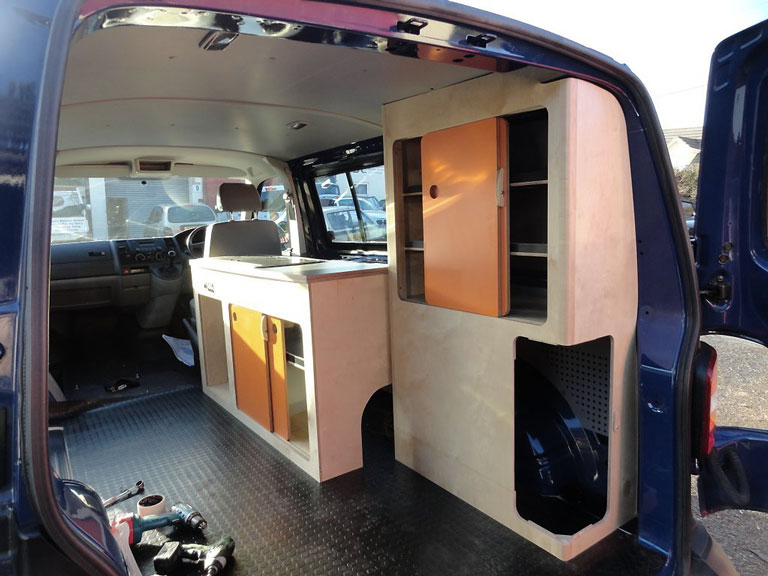 Campervan kitchen units installation using plywood looking from rear doors