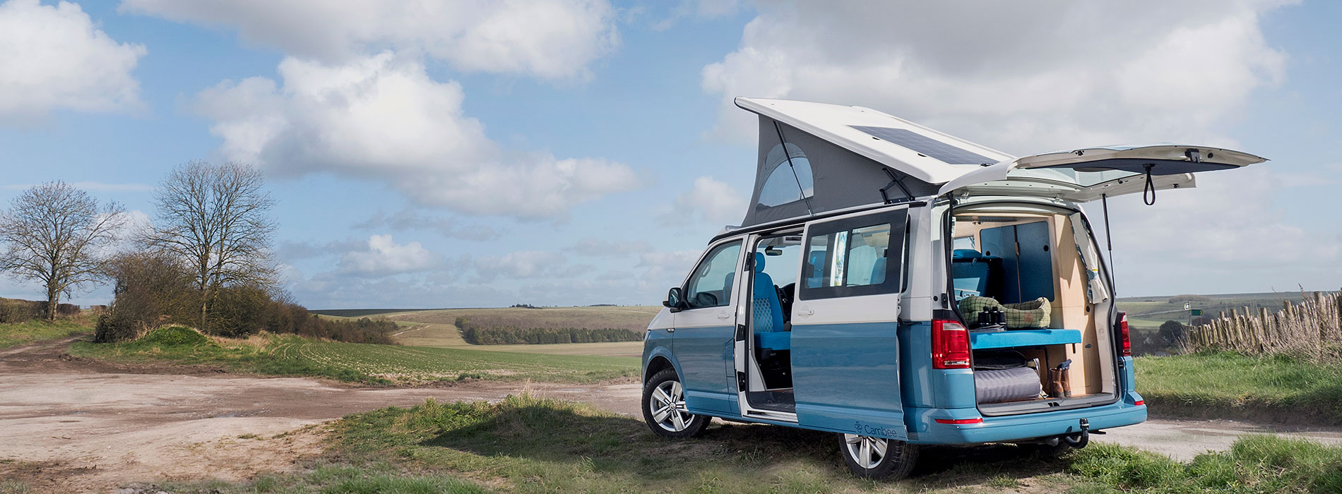 Side view of blue and white parked T6 campervan showing sliding doors and boot open with elevated roof up int he countryside