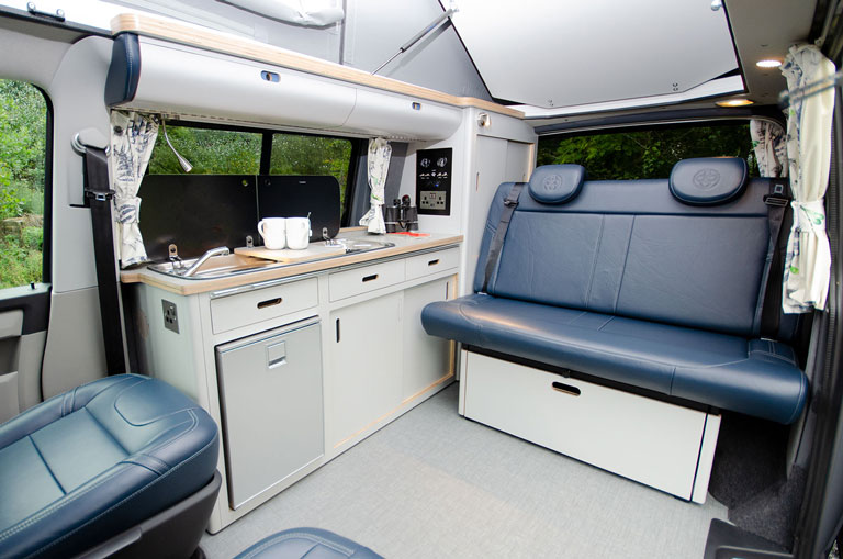 Camper interior with navy blue leather seats and kitchen bespoke conversion
