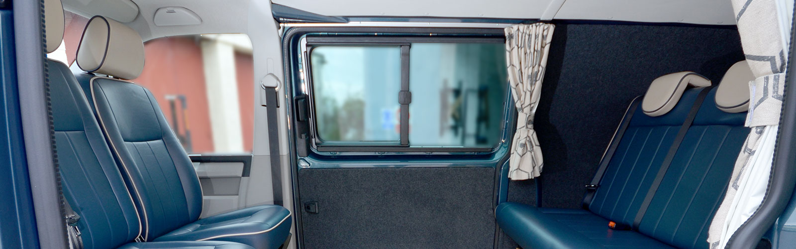 Blue leather rock and roll seat with cream headrests with blue piping and tied back curtains