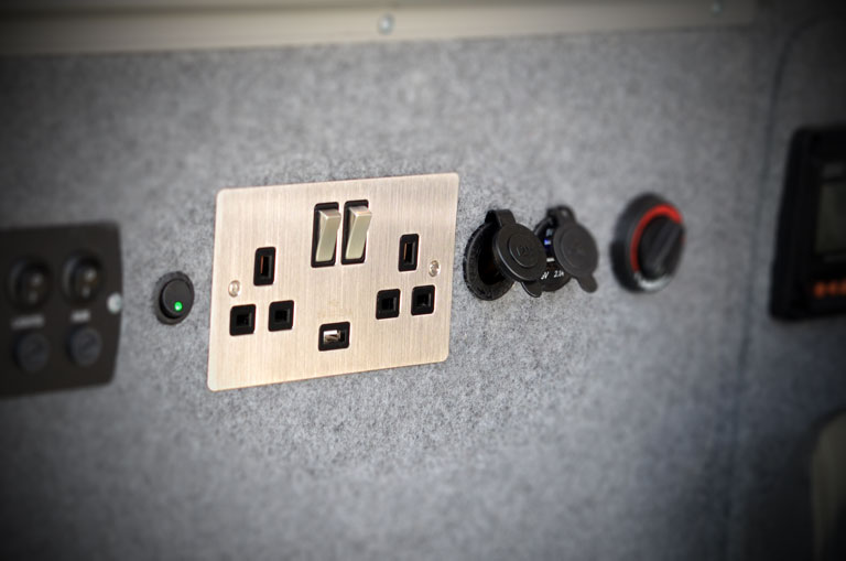 Ambience controls and silver plug socket in campervan