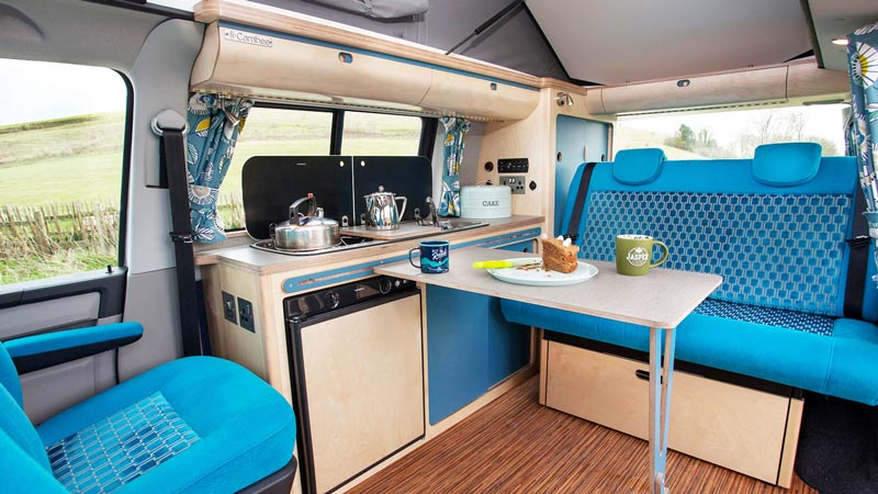 Camper conversion of slide-out kitchen table and blue luxury upholstery seats with cake and tea