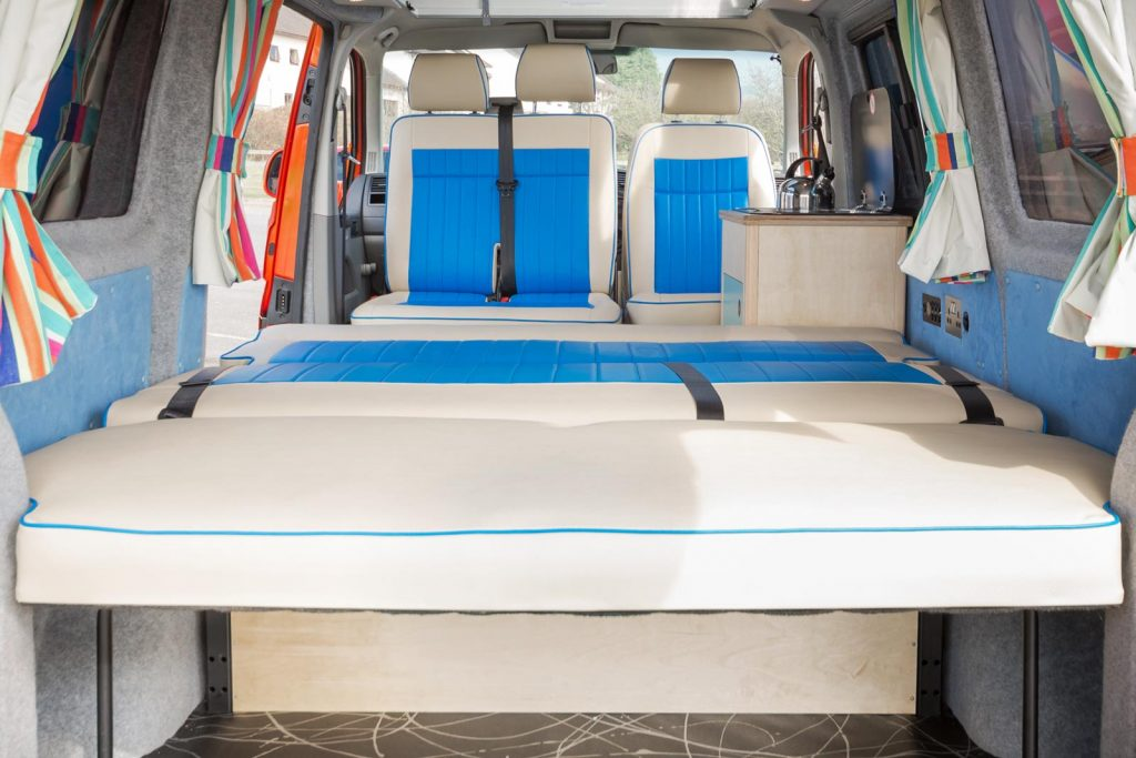 converted van with blue and white two tone seats showing front seats swivelled around and bed down