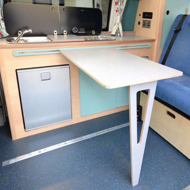 Campervan interior showing beautifully designed table leg in birch plywood