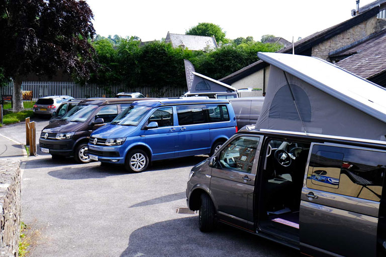 Side view of campervan parked with elevates roof up and sliding doors open