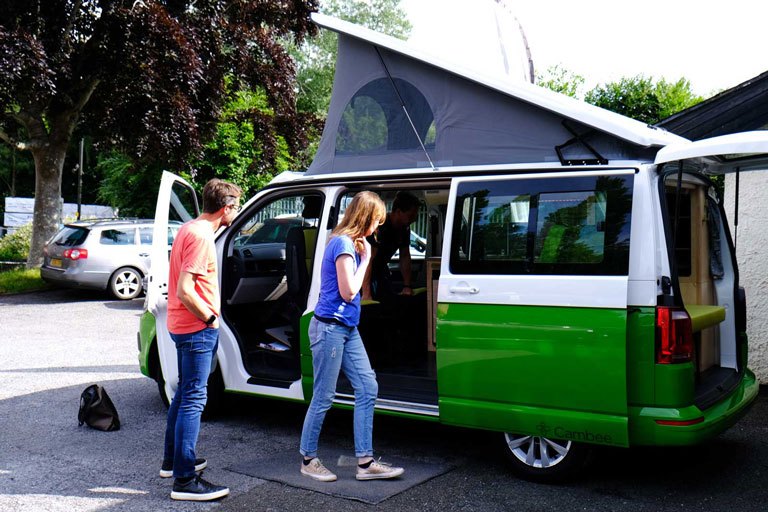 Two tone green and white VW T6 campervan conversation parked with elevated roof up and side doors open