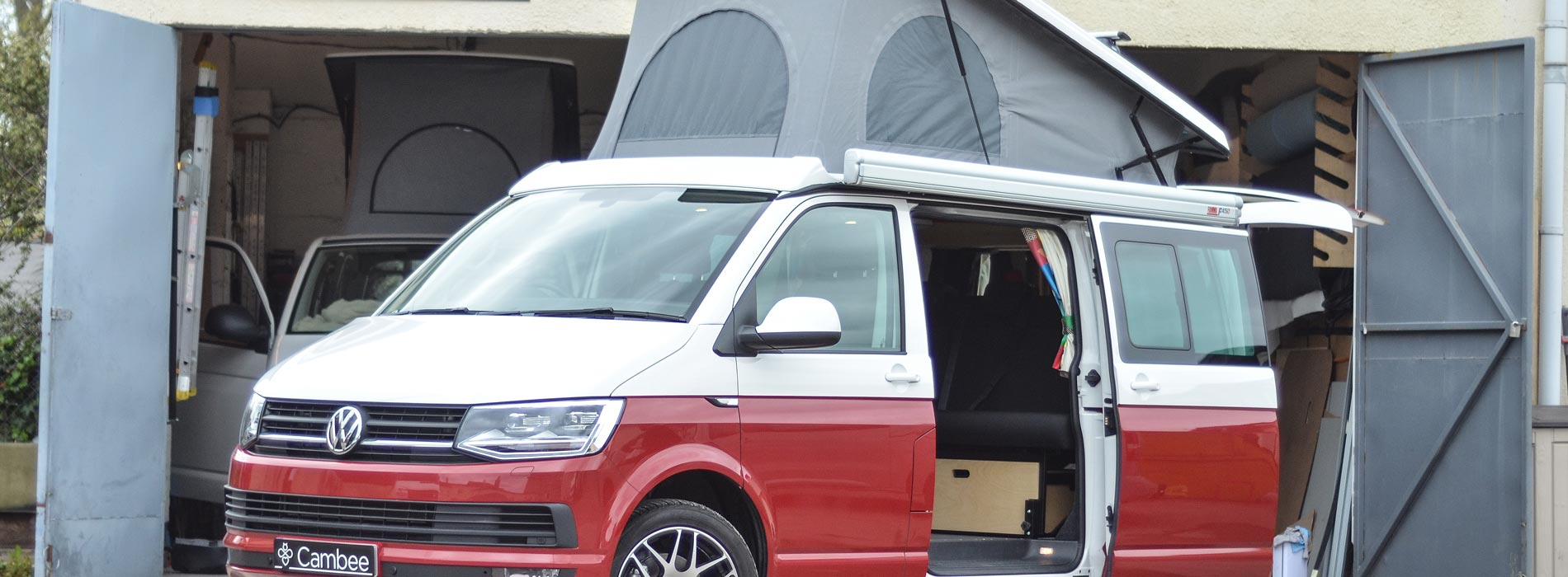 two tone red and white VW conversion campavan with doors open and pop top