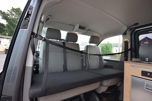 Campervan kids bunk shown with double passenger seat and safety net