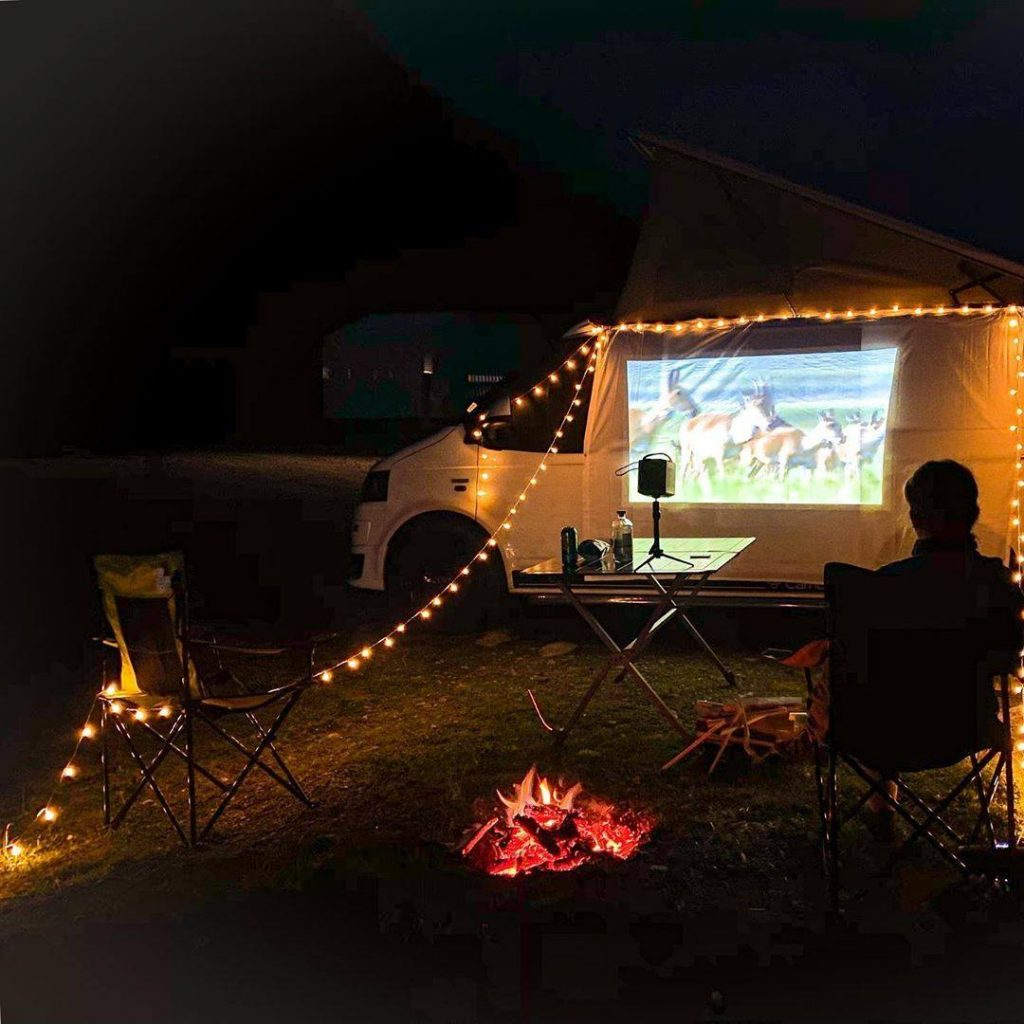 Movie being projected onto the outside of a campervan