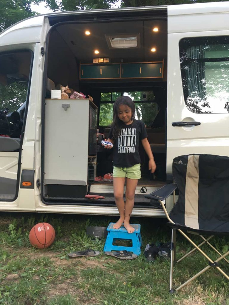 Young girl stepping out of a campervan