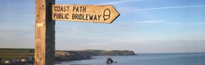 South West Coast Path sign with Thurleston in the background