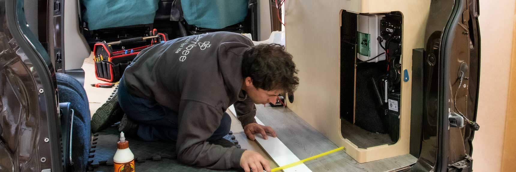 Cambee campervan fitter at work measuring for bespoke interior