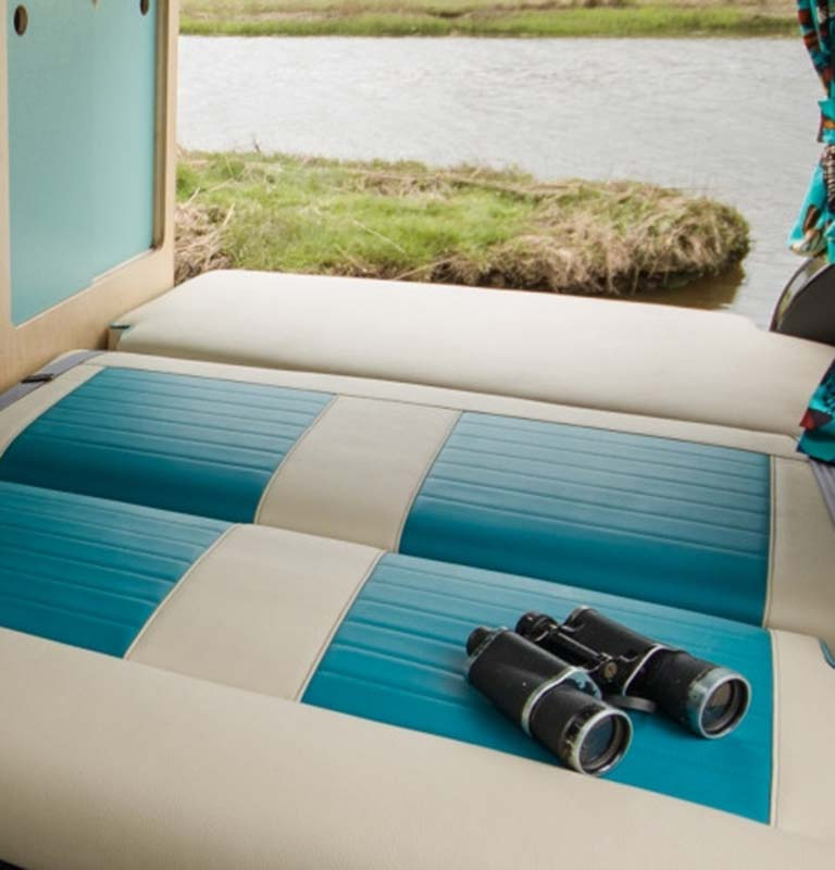 Two-tone campervan interior with rock and roll bed down, binoculars parked in nature