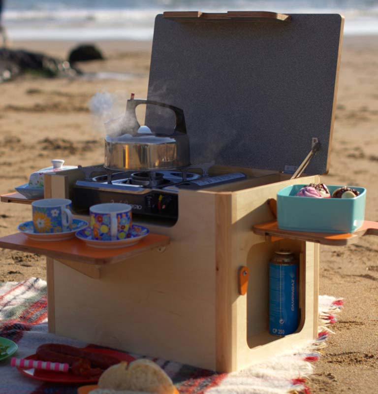 Very clever campervan bespoke birch plywood portable kitchen unit on the beach with gas stove