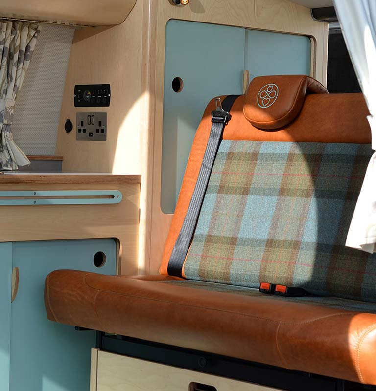 Leather and tartan cool bespoke campervan seats with bespoke eco plywood kitchen units and storage