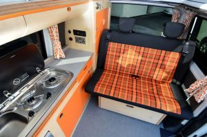 Funky orange and navy tartan bespoke campervan interior with eco birch plywood bespoke storage units from elevated roof